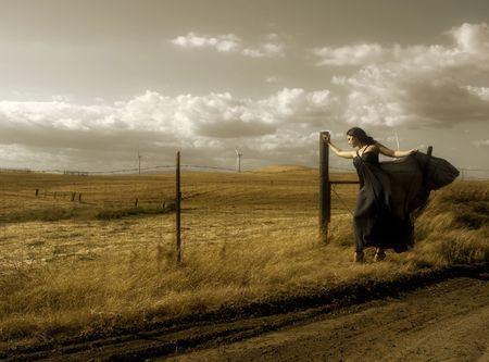 windy energy: Girl with a designer silk dress near the wind turbines