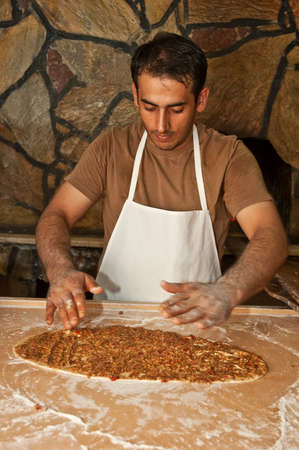 A cook making a traditional Turkish pizza (lahmacun) with meat next to a wood oven Stock Photo - 6073612