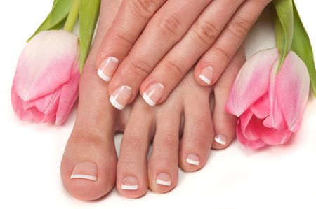 Pedicured feet and manicured hands with Easter tulips photo