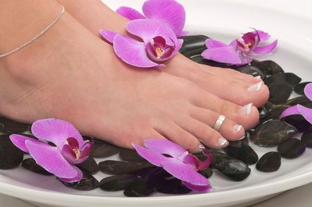 Pedicured feet and orchids photo