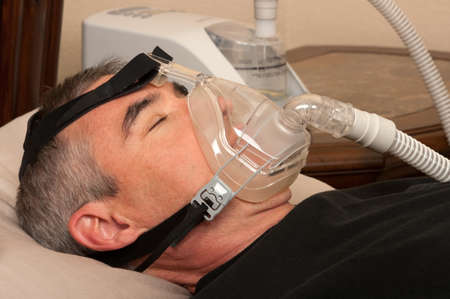 Man with sleeping apnea and CPAP machine photo
