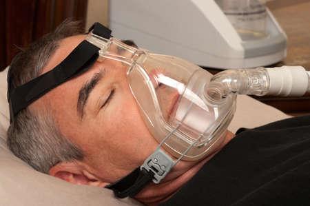 sleep: Man with sleeping apnea and CPAP machine