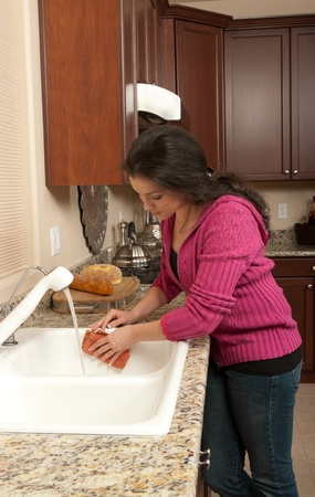 Young woman cleaning the sink photo