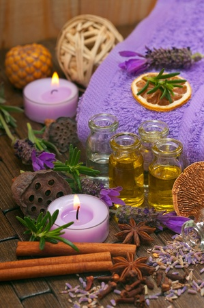 Spa concept with massage oils, aromatic lavender, spices, candles and cotton towels Stock Photo
