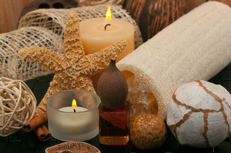 massage oil: Spa concept  with aromatic candles, massage oil and loofah