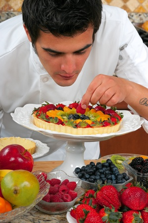 Young handsome chef making fruit tarts photo
