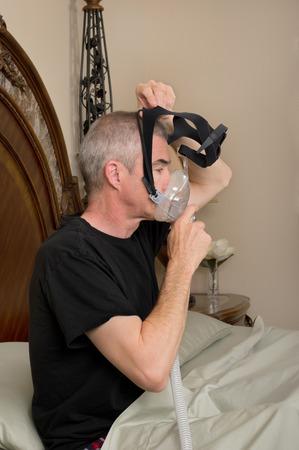Man wearing his CPAP machine before sleeping photo