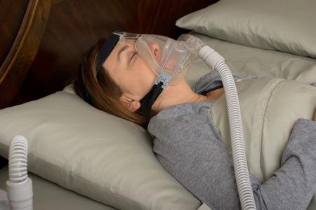 apnea: Donna che porta CPAP macchina per apnea del sonno