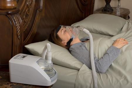 sleep: Woman wearing CPAP machine for sleep apnea