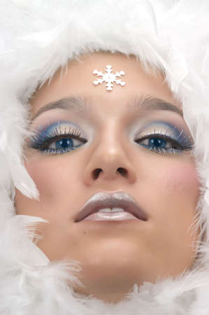 Girl with beautiful make up, white feathers and snow flake