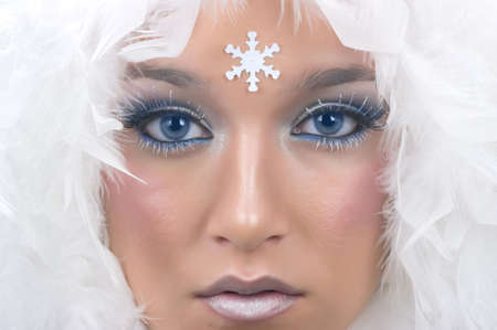 winter fashion: Girl with beautiful make up, white feathers and snow flake