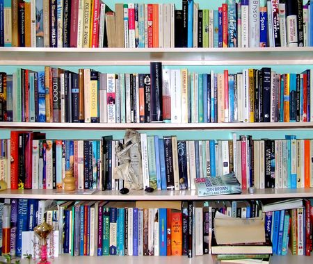 Book shelf on a blue wall with many multicolor books Stock Photo