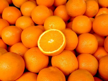 Big pile of oranges with one cut in half at the top Stock Photo