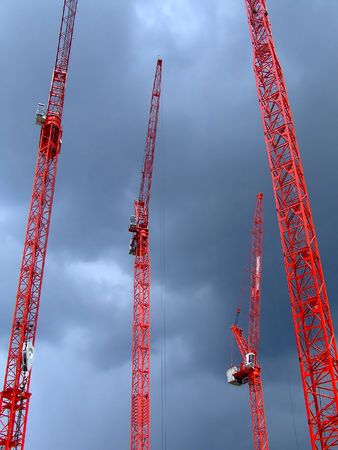 automat: Four tall red cranes with sky in background Stock Photo
