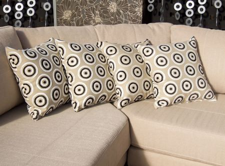 upholster: Four beige velvet pillows with circle decoration on the sofa