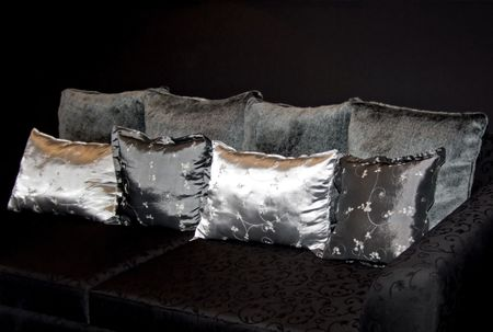 Unusual fur and silk pillows on the black sofa Stock Photo - 697373