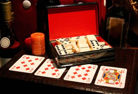 Box of dominoes and playing cards on the leather mate