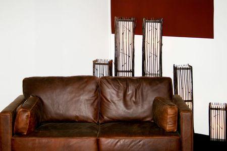 brown leather sofa: Real divano in pelle marrone con lampade decorative