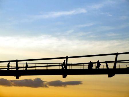 Silhouette of walking people and pedestrian bridge photo