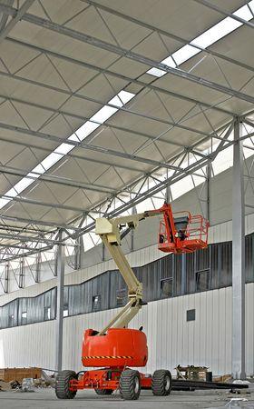 Portable construction crane in big industrial hall