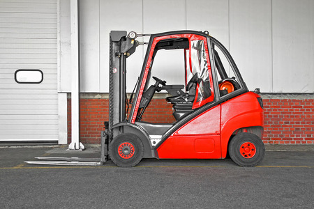 lifter: Big red fork lifter truck in storehouse Stock Photo