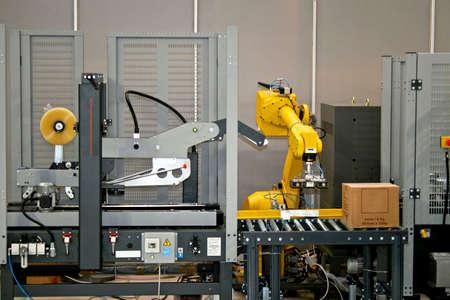 mano robotica: L�nea de envasado con el brazo rob�tico en el trabajo