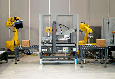 packaging industry: Two robotic hands simultaneous work at packaging line Stock Photo