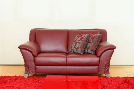Dark red leather sofa over white wall photo