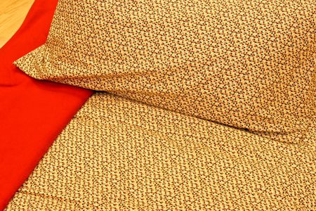 Red and beige sheets and pillows detail photo