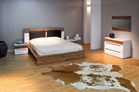 Bedroom with big double bed and real cow fur Stock Photo - 2409261