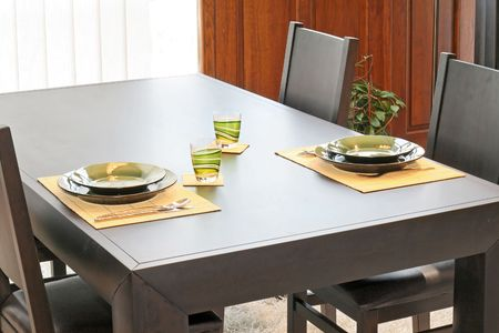 Modern black dinning table with green plates Stock Photo - 2415983