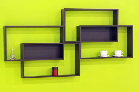 Geometric brown wooden shelves over green wall  