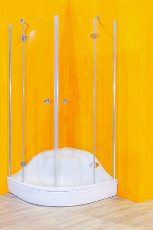 Corner shower cabin with glass wall and yellow background photo
