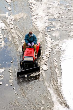 Man operating machine removing snow from street photo