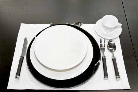 Porcelain dishes with tableware at black table  photo