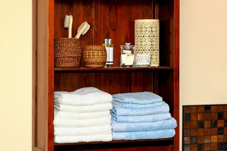 neat: Organized bathroom shelf with cotton towels and toiletries