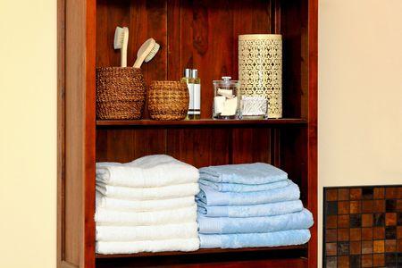artigos de higiene pessoal: Organized bathroom shelf with cotton towels and toiletries