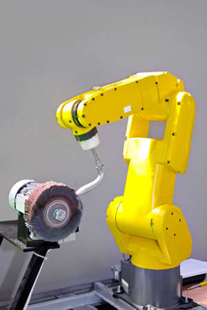 Yellow robotic arm for automatic operations in factory photo