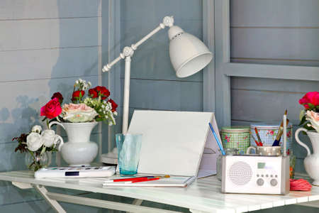 Creative mess on a white wooden desk photo