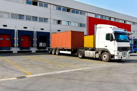 carga: Descarga de grandes contenedores camiones en edificio de almac�n  Foto de archivo