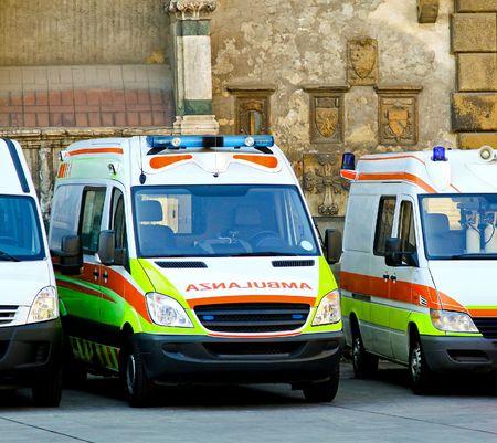 nhs: Ambulance paramedic team with several emergency vehicles Stock Photo