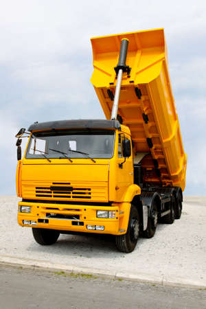 loads: Big yellow construction tipper truck discharging loads