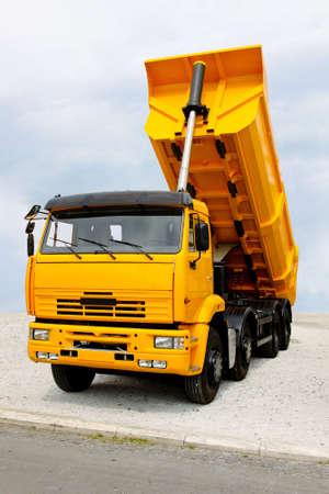 dumper: Big yellow construction tipper truck discharging loads