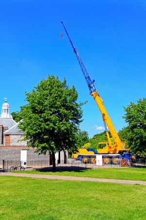 Green tree in front of construction crane    photo