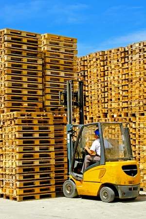 loads: Forklift operator lifting bunch of wooden pallets