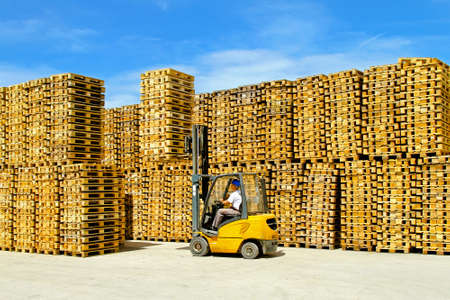Forklift operator inside row of wooden euro pallets