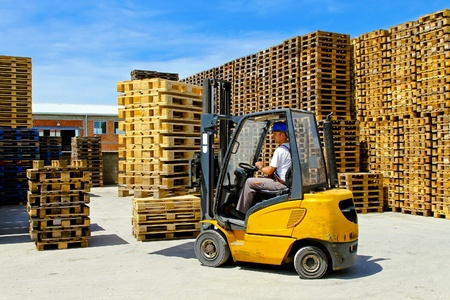 loads: Forklift operator handling wooden pallets in warehouse