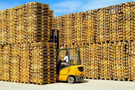 Forklift operator inside row of wooden euro pallets Stock Photo - 8518961