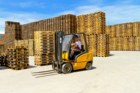 Forklift operator in pallet warehouse on the open  photo