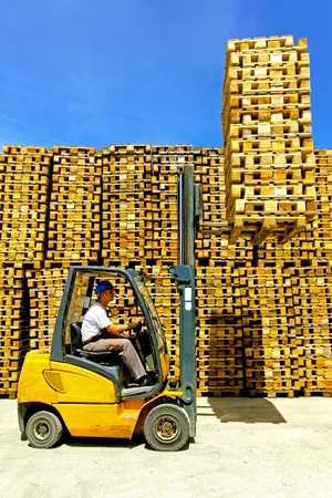 euro pallet: Man operating forklift lifting bunch of euro pallets  Stock Photo